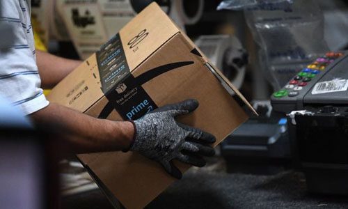 A worker holding an amazon box